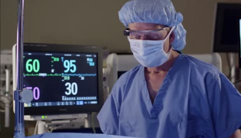 Anesthesiologist activating Google Glass by touching the glasses.